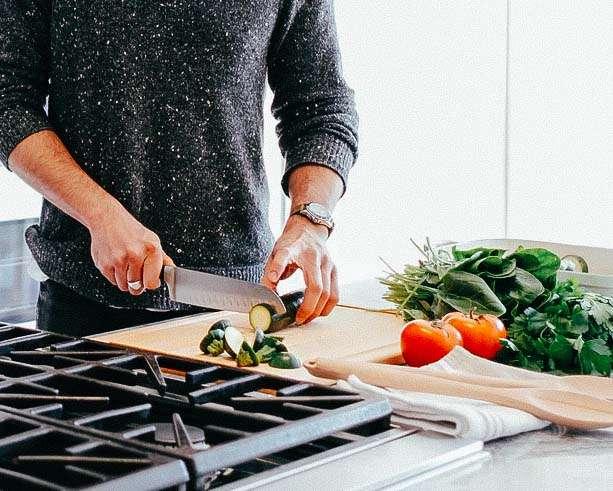 hombre cocinando comida real y natural